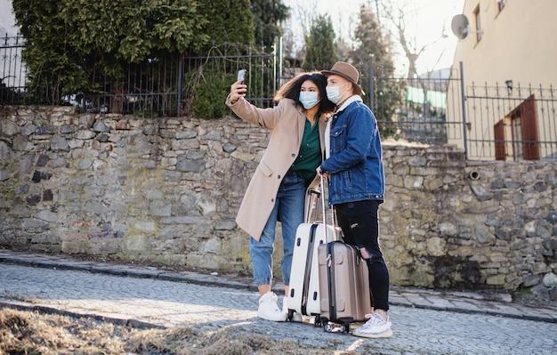 旧市街の通りでスマートフォンでselfieを取る荷物を持つ若いカップルの観光客
