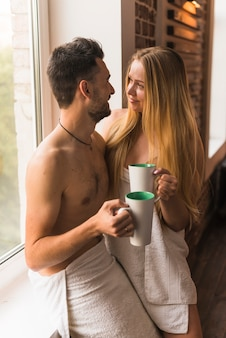 Young couple in towel holding coffee mug near the window