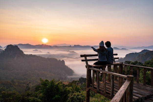 Young couple traveler looking at sea of mist and sunset over the mountain at mae hong son, thailand