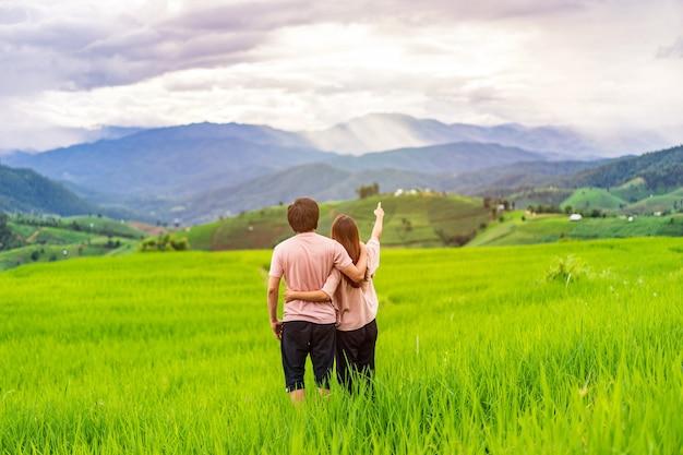 タイの美しい緑の棚田フィールドを楽しんで見て休暇中の若いカップルの旅行者