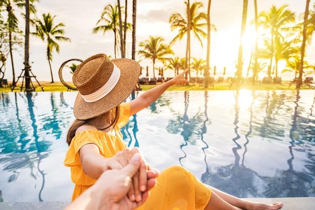 여름 휴가를 여행하는 동안 열대 리조트 수영장에서 휴식을 취하고 일몰을 즐기는 젊은 커플 여행자