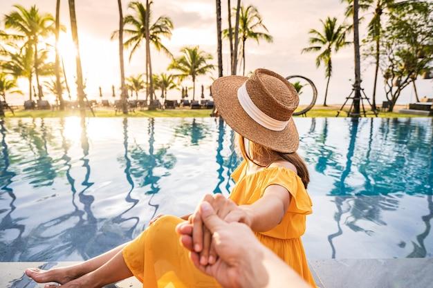 Молодая пара путешественник расслабляется и наслаждается закатом у бассейна тропического курорта во время путешествия