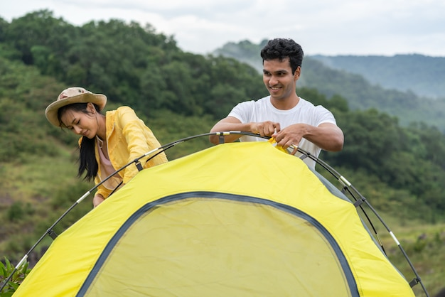 Young couple traveler setting a tent for camping outdoor on holidays vacation in summer