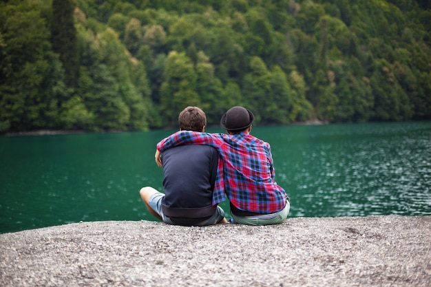 Young couple of travelers admires a mountain lake, rear view