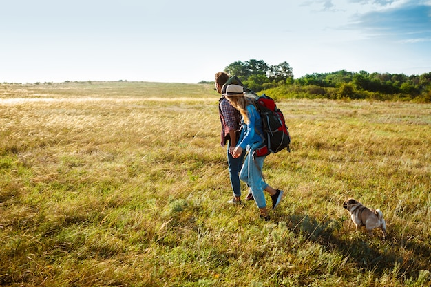Young couple of travelers walking in field with pug dog