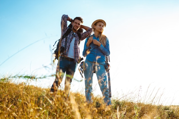 Young couple of travelers with backpacks smiling, standing in field