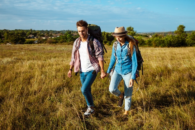 Young couple of travelers with backpacks smiling, walking in field