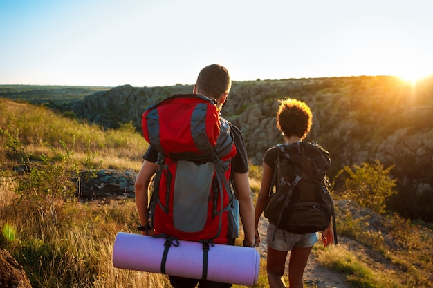Young couple of travelers with backpacks traveling in canyon at sunset