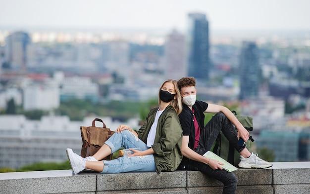 休日に街のカメラ、コロナウイルスの概念を見て地図を持つ若いカップルの旅行者。