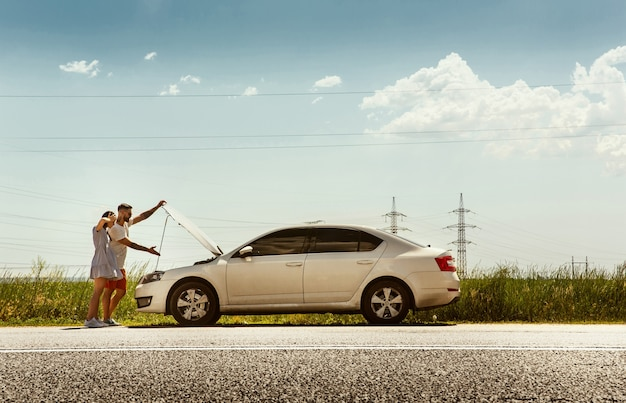 Giovani coppie che viaggiano in macchina in una giornata di sole