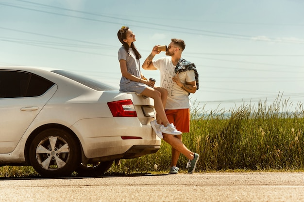 Young couple traveling on the car in sunny day