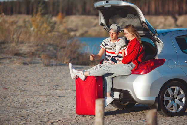 Young couple traveling on the car. woman and man having a trip on automobile. happy young people outdoors.