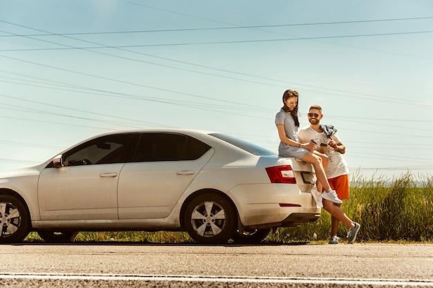 화창한 날에 차를 타고 여행하는 젊은 부부