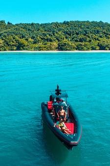 若いカップルが紺碧の海をモーターボートで旅する