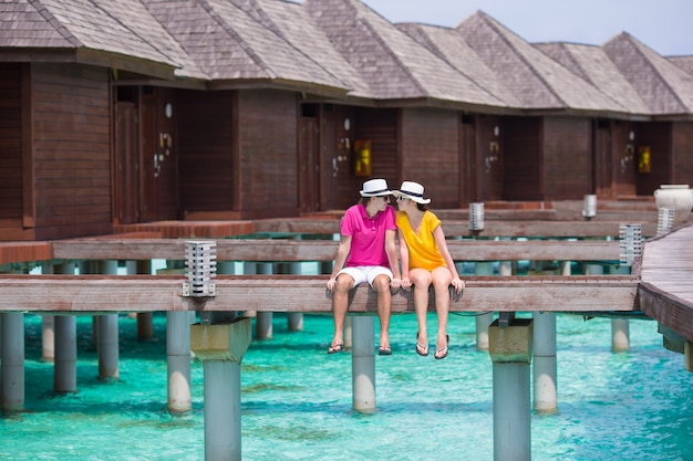 Young couple on tropical beach jetty near water bungalow