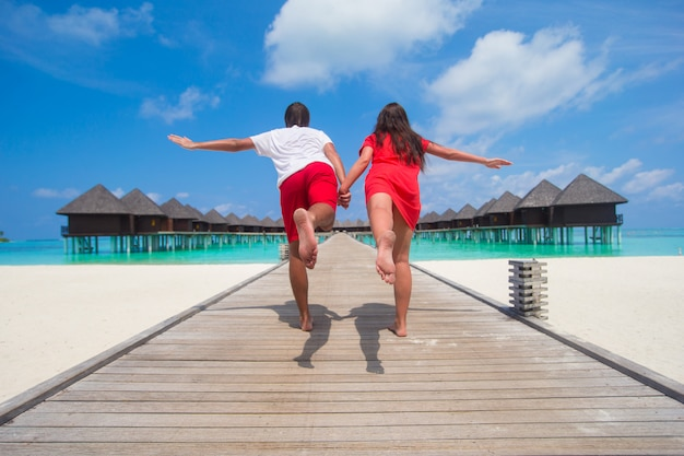 Young couple on tropical beach jetty at perfect island