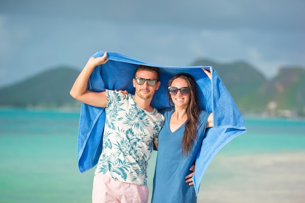 Young couple at tropical beach under the towel hiding from tropical rain.