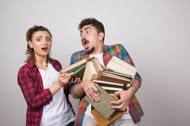 Young couple trying to hold a lotof books on gray wall