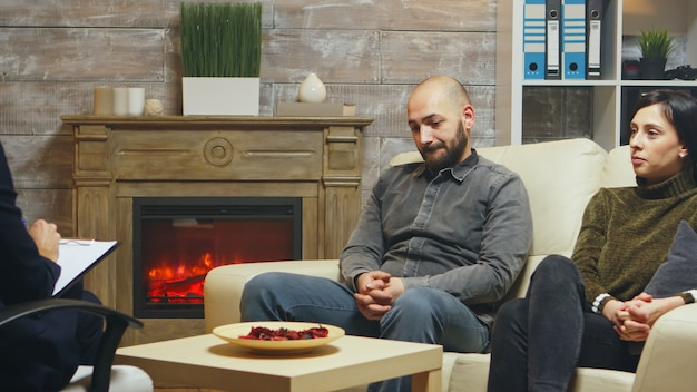 Young couple trying to save their relationship talking with a psychoanalyst sitting on couch.