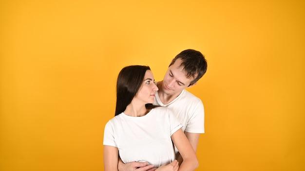 Молодая пара, двое друзей, парень, девушка в белых пустых пустых дизайнерских футболках, обнимаются, изолированы на желтом