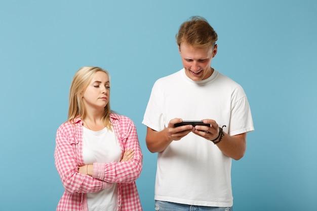 Молодая пара, двое друзей, мужчина и женщина в белых розовых пустых пустых футболках, позируют