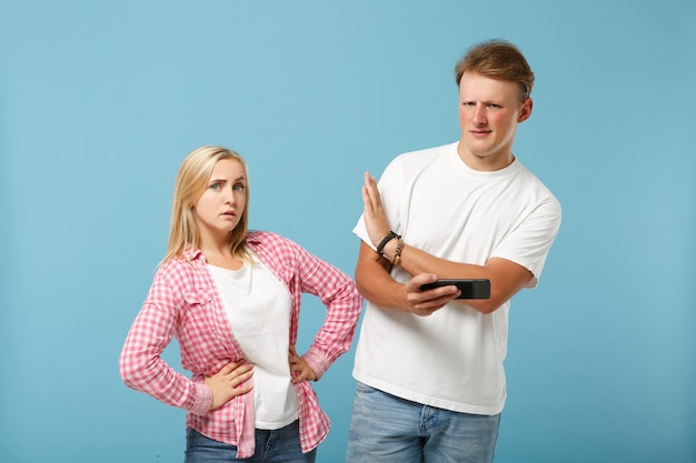 Young couple two friends man and woman  in white pink empty t-shirts posing
