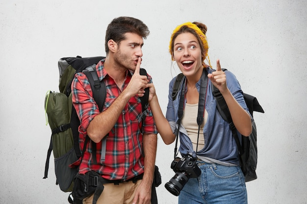 Young couple of two hikers equipped with tourist accessories and backpacks enjoying adventurous journey: bearded man making shh sign with finger, asking his excited girlfriend to keep silent