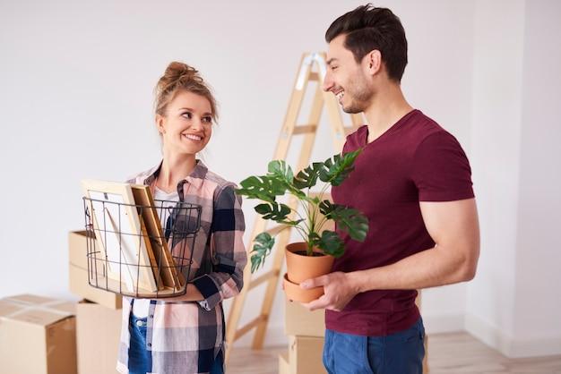 Молодая пара распаковывает коробки со своими вещами в новой квартире
