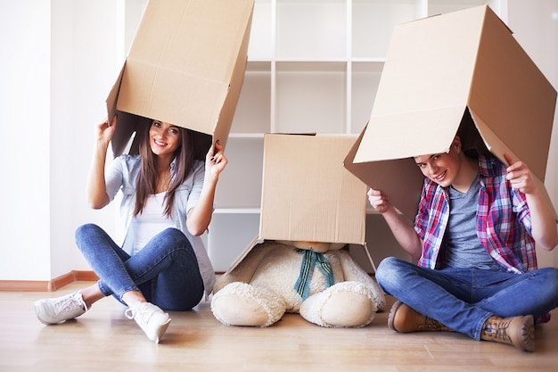 Young couple unpacking cardboard boxes at new home. moving house