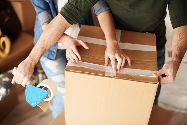 新しいアパートで移動ボックスを開梱する若いカップル