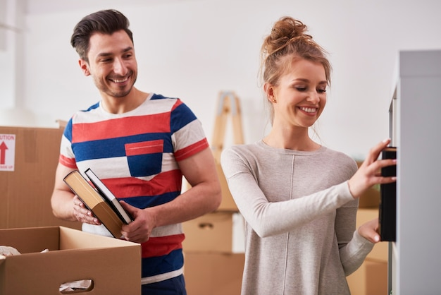 Young couple unpacking moving boxes in new flat