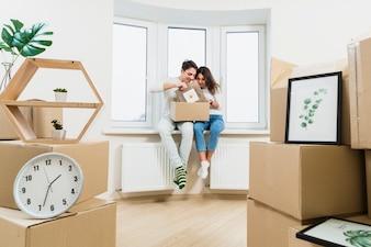Молодая пара распаковывает картонные коробки в своем новом доме