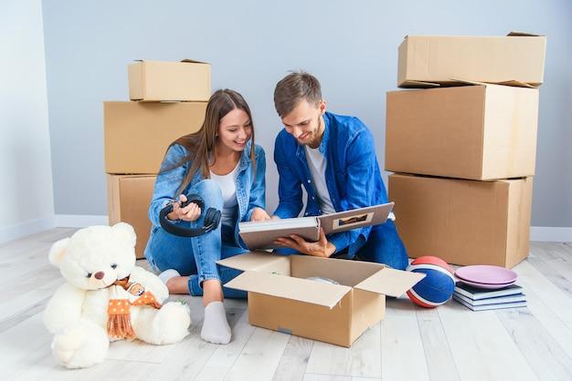 Молодая пара распаковывает вещи после переезда в новый дом