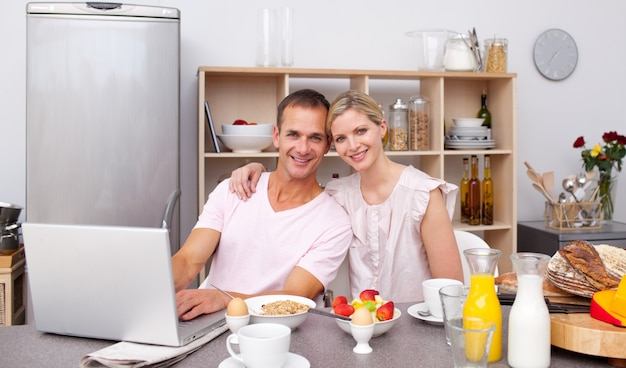 Молодая пара, используя ноутбук, имея завтрак