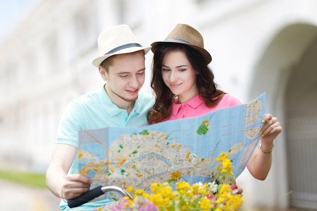 지도를 사용하고 도시에서 자전거를 타는 젊은 부부 프리미엄 사진