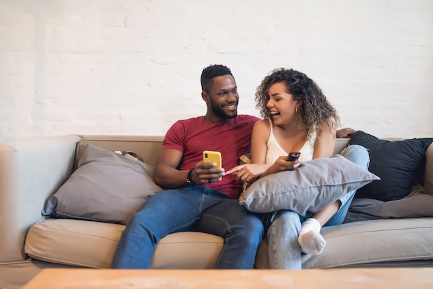 自宅のソファに座って一緒に携帯電話を使用している若いカップル。 Premium写真