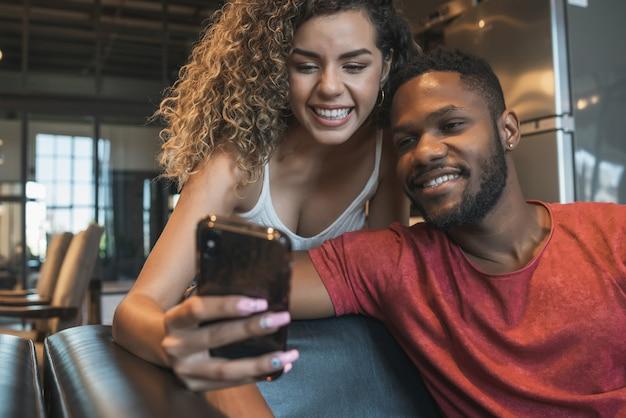 自宅のソファに座って携帯電話を使用している若いカップル。