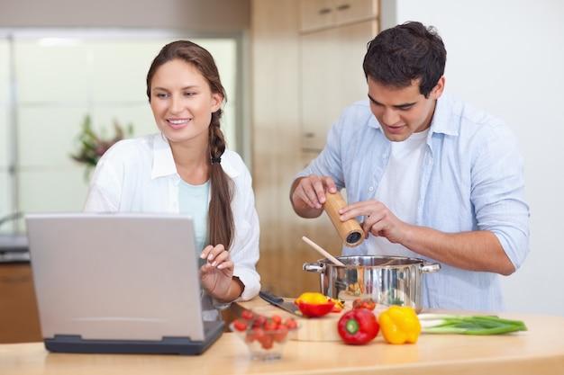 Молодая пара, используя ноутбук, чтобы приготовить