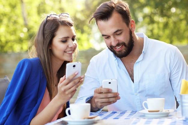 レストランで携帯電話を使用して若いカップル
