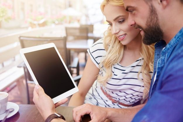 Giovani coppie che per mezzo della compressa digitale al caffè