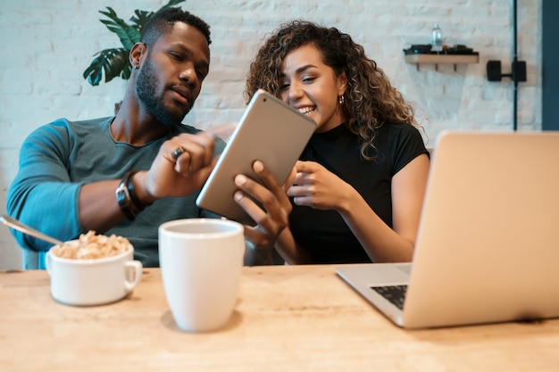 Young couple using a digital tablet and a laptop while having breakfast together at home. Free Photo