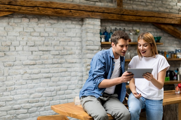 Young couple using a digital tablet and smiling while sitting on the table at home