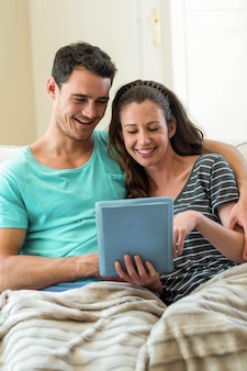 Young couple using digital tablet on sofa at home