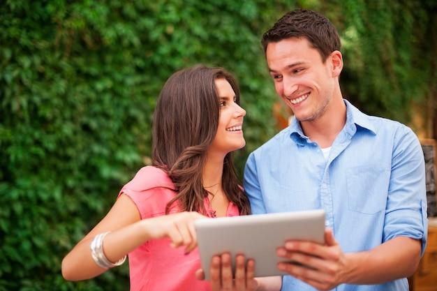 Молодая пара с помощью цифрового планшета