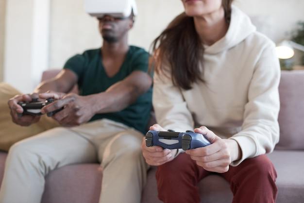 ジョイスティックを使用して、部屋のソファで一緒にビデオゲームをプレイする若いカップル