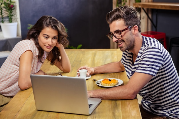 Young couple using laptop in cafeteria