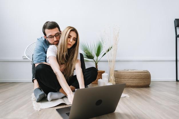 ラップトップコンピューターを使用して、情報を閲覧し、モダンなリビングルームでラップトップの画面を見ている若いカップル。