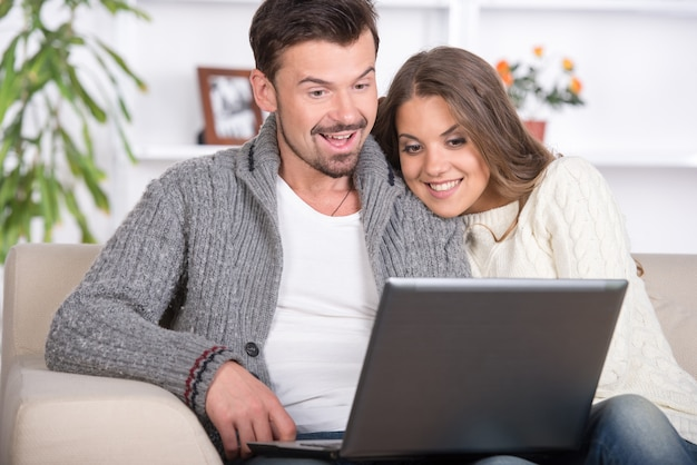 Young couple using a laptop computer at home.
