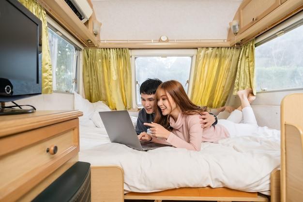 캠핑카 rv 밴 캠핑카의 침대에서 랩톱 컴퓨터를 사용하는 젊은 부부