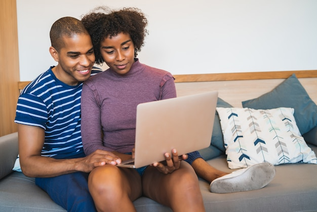 Young couple using laptop on couch at home.